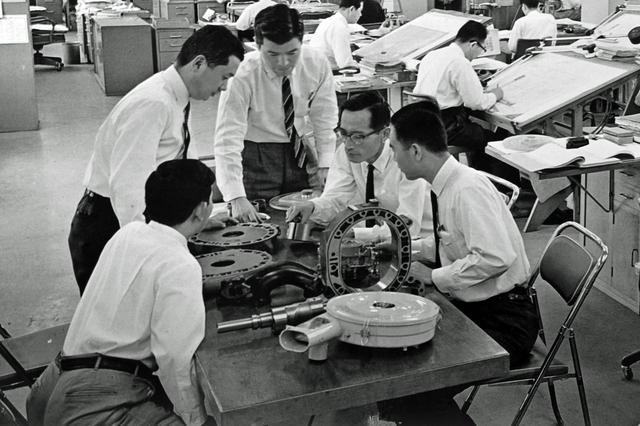 画像: 山本さん(右から2番目)がローター部分を手に、RE研究部員とミーティングしている。初期のロータリーには解決しなければならない問題が山積していた。