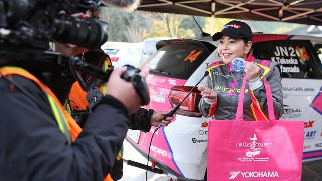 画像: メディアの取材に答える竹岡圭さん。ノベルティのバッグも鮮やかなピンク色。