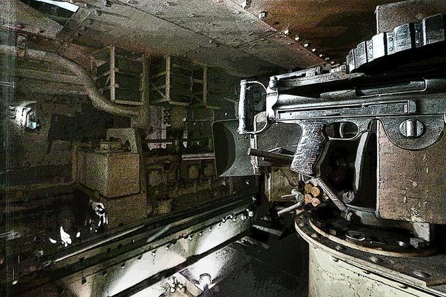 画像: 左右に張り出した砲塔後方の乗降扉を入るとすぐに7.7mm機銃がある。その前方が6ポンド/57mm砲(画像では見えない)。中央に直6エンジンの後半部が見えている。左側に箱型オイルタンクと始動用クランクハンドルも見える。内部は激しい轟音と振動、硝煙と排ガスの暗闇だ。