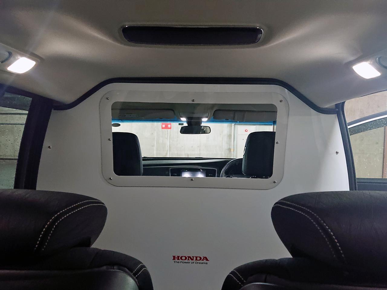 画像: 車両内部に設置された、運転席と後部座席の仕切り。