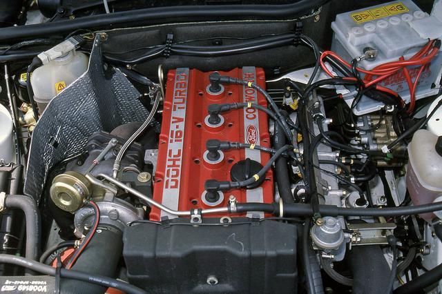 画像: 赤いヘッドカバーには「DOHC 16V TURBO」と「COSWORTH」のロゴが誇らしげに刻まれる。インタークーラーもエンジン前方に備わる。