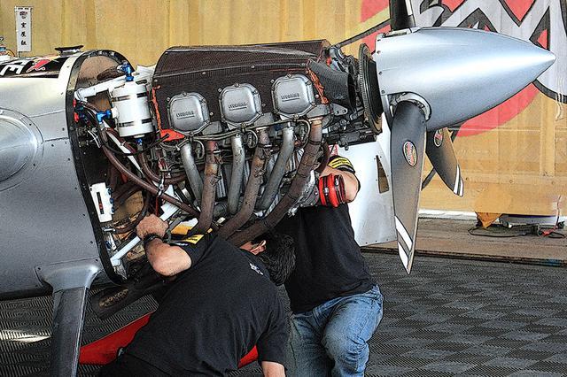 画像: 整備中の室屋機。シリンダー、吸排気マニホールドの配置がよくわかり、まるでエンジンの教材模型のようなシンプルさ。そして整備するメカニックと大きさを対比すると、いかにエンジンや機体がコンパクトかわかる。