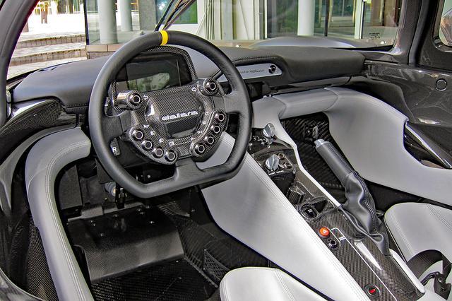 画像: カーボンファイバーとエコレザーを用いたインテリア。ステアリングにはウインカーやライトなどのスイッチ類を内蔵している。