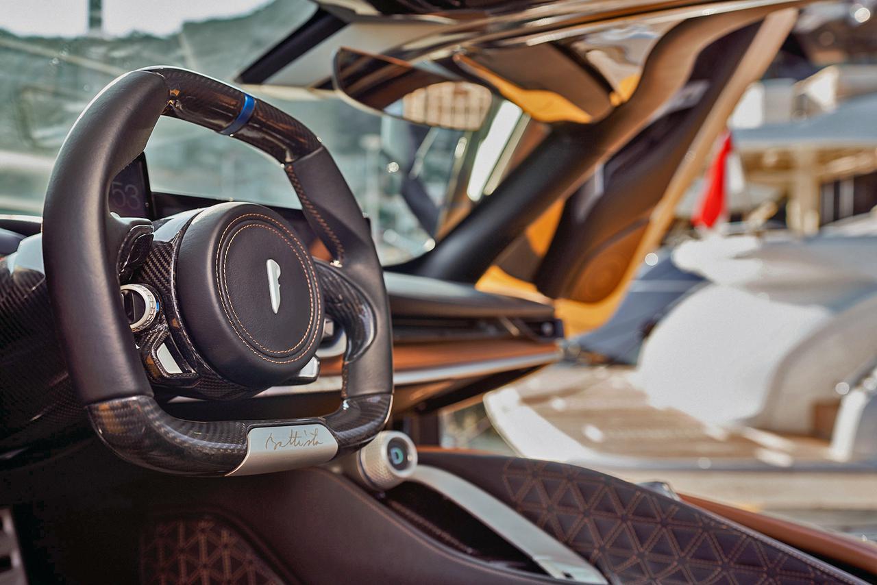 画像: 小径ステアリングには本革とカーボンファイバーを採用。計器類にはモニターを多用したデジタルコクピットとなっている。