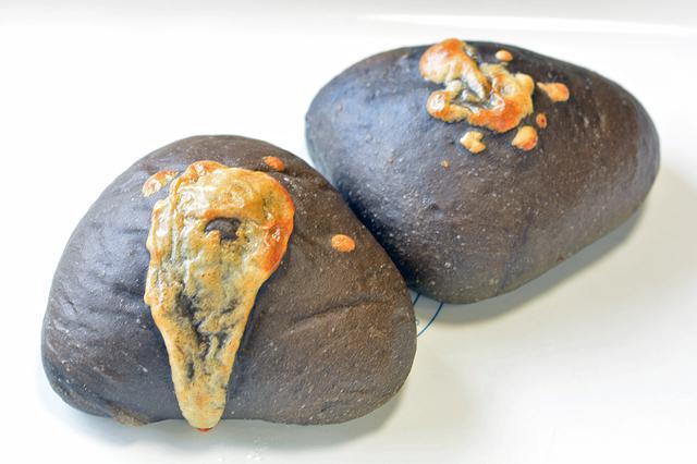 画像: 名称のとおり黒いパンが特徴の「黒カレー」(1個280円)。揚げパンではないので、さっぱりした口あたり。