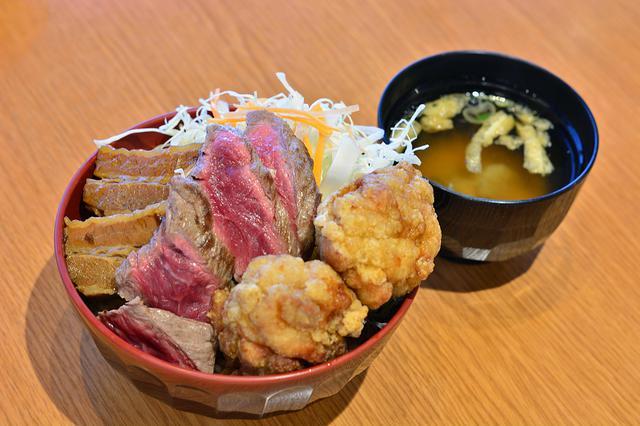 画像: 「肉処 壱丁田」の人気メニュー「肉! よくばり丼」(990円)。ビフテキ、豚の角煮、鶏の唐揚という3種の味が楽しめる。