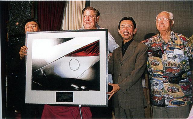 画像: 2000年6月のZCONラスベガスにて発表されたZ33のイメージスケッチ。左からCPSの湯川氏、ZCCAディレクターの「マッド」・マイク氏、日産デザイン本部長の中村史郎氏(いずれも当時)、そして「Zの父」ことミスターK、故・片山 豊氏である。