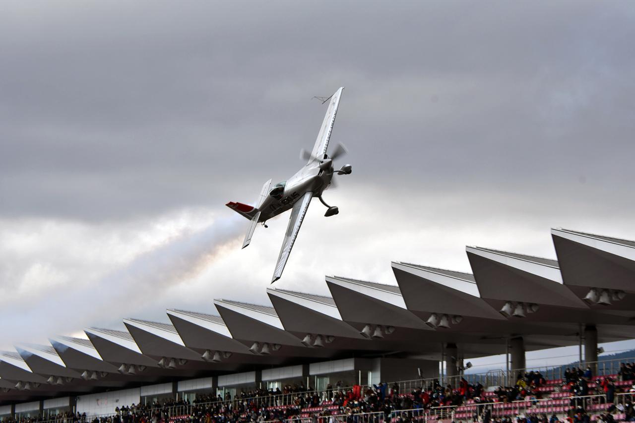 画像: 富士スピードウェイのホームストレート上を超低空飛行する室屋機。撮影:井上雅行(モーターマガジン社)