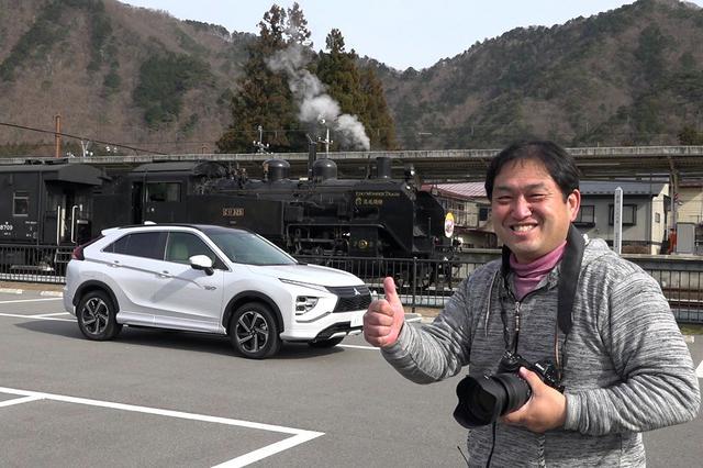 画像: 鬼怒川温泉駅前のパーキングで2台を仲良く並べご機嫌の助川氏。エクリプスクロスPHEVの運転席にはスタッフが待機。(体を伏せてもらってます)