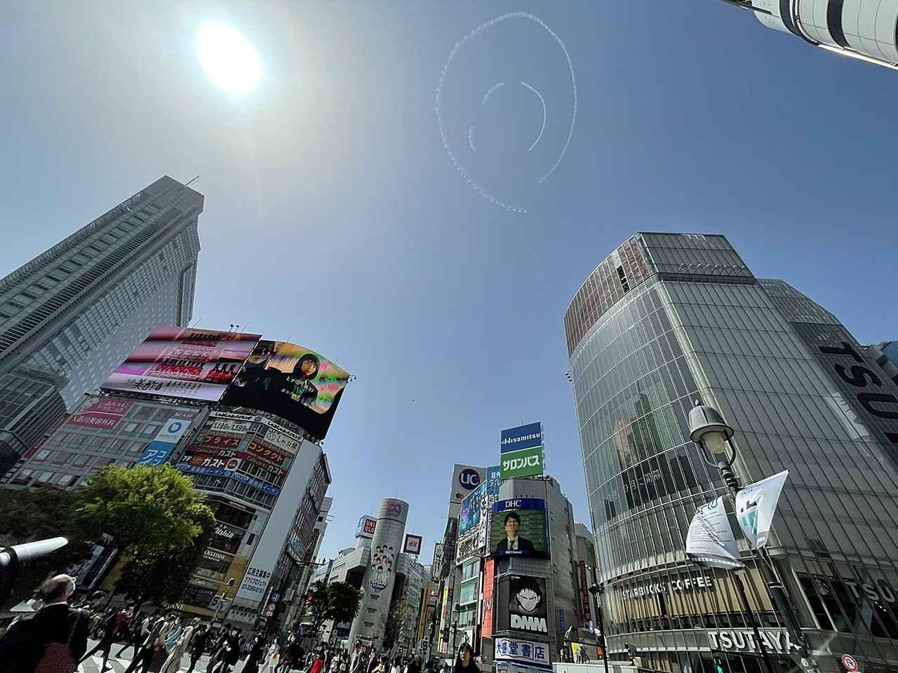 画像: 渋谷のスクランブルエッグ交差点上空に描かれたニコちゃんマーク。大勢の人が空を見上げていた。(Pathfinder)