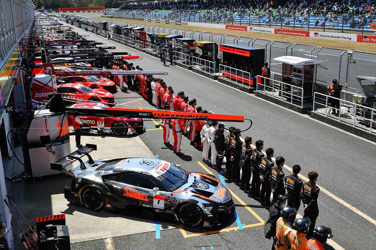画像: ピット前にチームクルーが整列し開幕セレモニーを迎える。