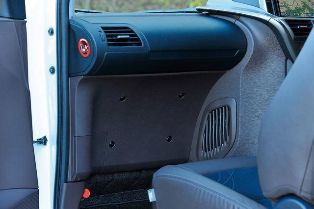 画像: 通常助手席前にあるエアコンユニットを小型化しセンタークラスター内に収納したことで助手席インパネを大きく削り、足元スペースを拡大。オフセットして座ることで後席左側乗員の膝スペースも確保している。
