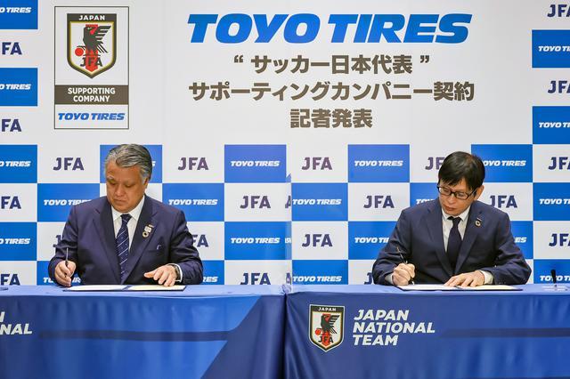 画像: 契約書にサインする、JFAの田嶋幸三 会長(左)と、トーヨータイヤの笹森建彦 取締役。