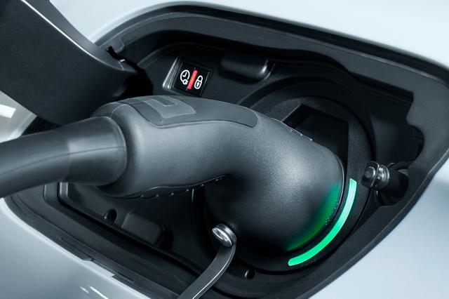 画像: 充電は専用充電ケーブルで行う。充電ソケットは車輌左後方にあり、ソケット脇のLEDインジケーターに、スタンバイ(白)、充電中(緑の点滅)、充電完了(緑の点灯)、青(充電予約中)など状態が表示される。