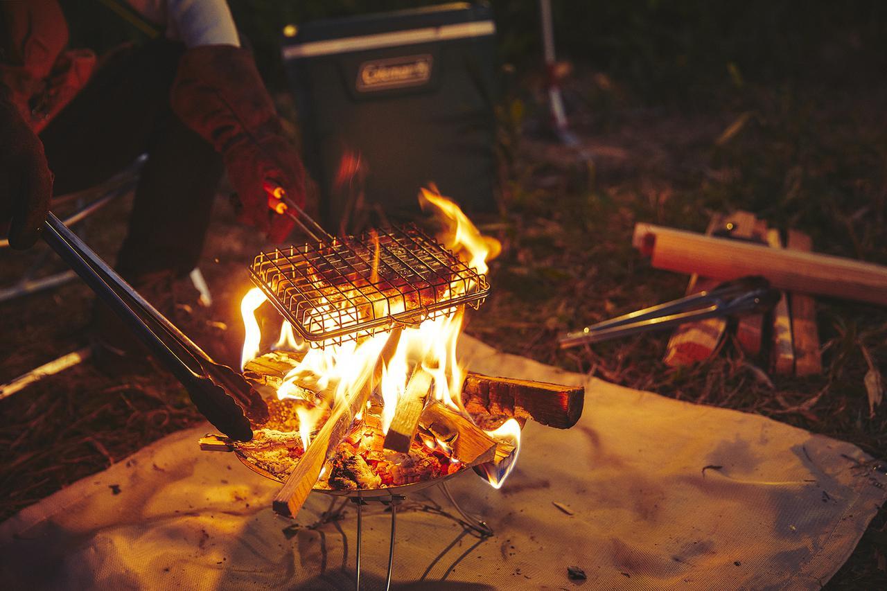 画像: 焚き火料理に開発された「グリルバスケットクッカー」に、肉やパンを挟んで豪快に炙りながら調理できる。
