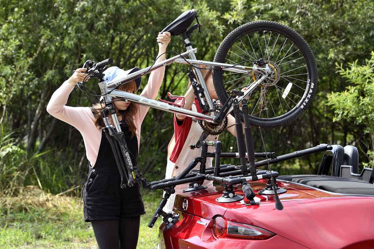 画像: 自転車のフロントホイールをはずし、フレーム&アホイール部からキャリアに積む。男性ならひとりでもできるが、女性は二人でやったほうが無難かも。