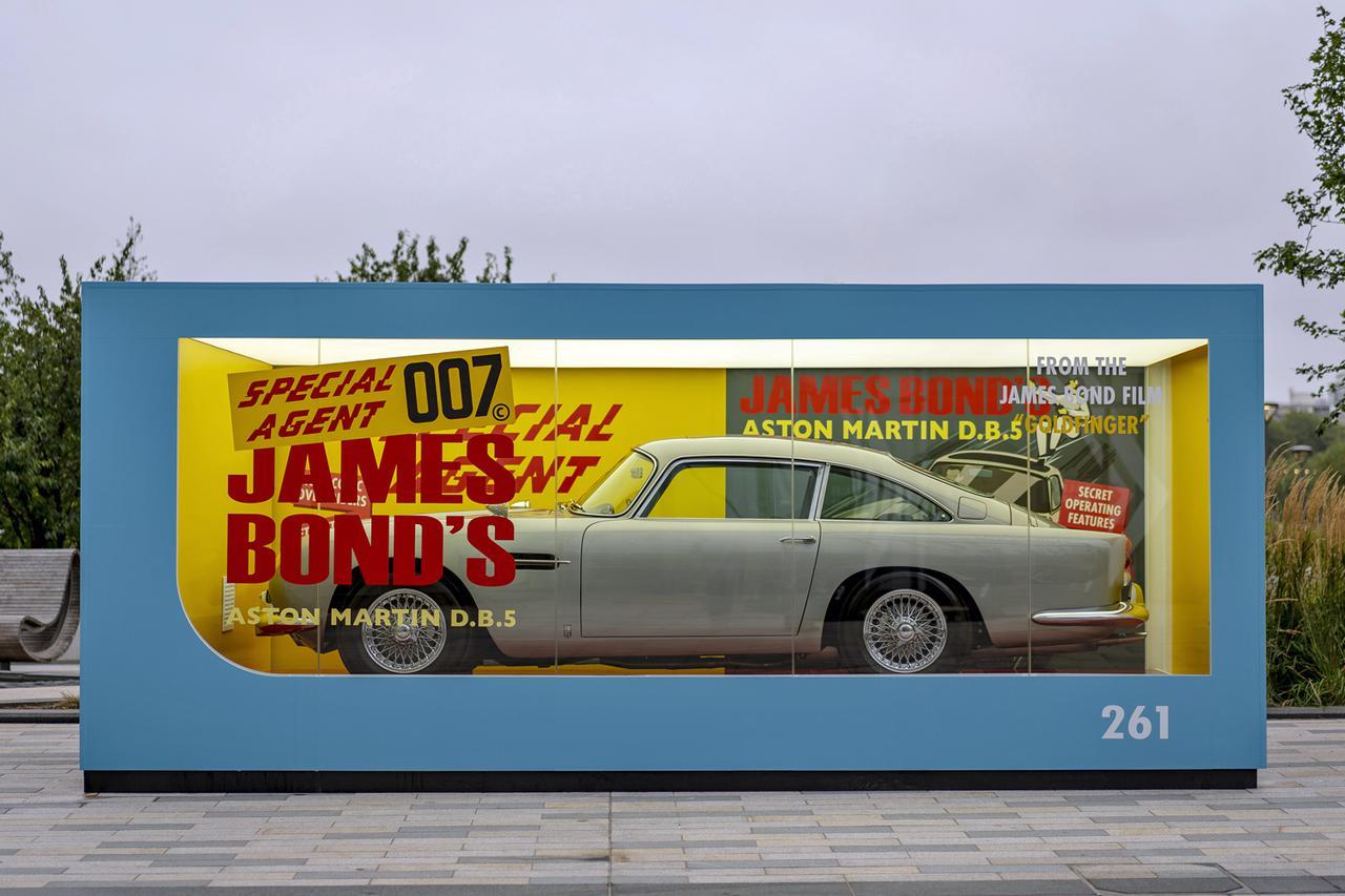 画像: 実車をミニカーに見立てて巨大なパッケージに入ったボンドカーのレプリカ。