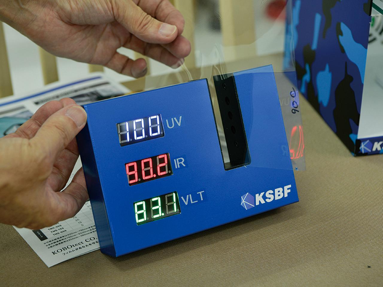 画像: スリット部にフィルムを差し込むと、上から紫外線遮蔽率、赤外線遮蔽率、可視光線透過率を表示する装置。