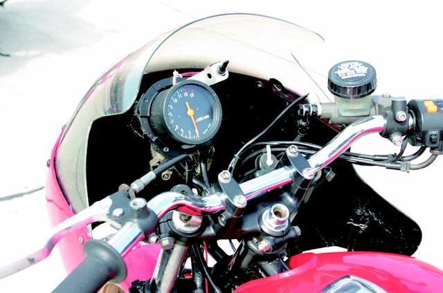 画像: アップハンドルに、ハーフフェアリングを組み合わせたコクピットまわり。レギュレーションに従い、ヘッドライトには100mm径以上の製品を装着している。レブカウンターのレッドゾーンは12,000rpmから。 オートバイ/モーターマガジン社
