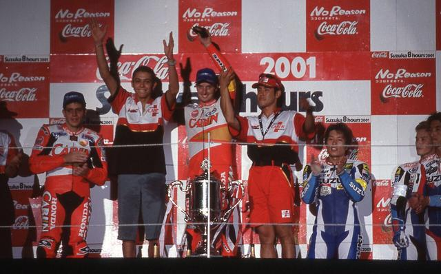 画像: C.エドワーズ(中央)、V.ロッシ(中央から左)とともに、2001年大会の表彰台の中央に立つ鎌田学(中央から右)。 www.suzukacircuit.jp