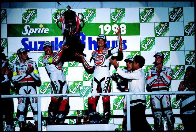 画像: 1998年、表彰台のてっぺんで、笑顔を見せる伊藤/宇川組。同一ペアによる連覇は、この大会が初でした。 オートバイ/モーターマガジン社