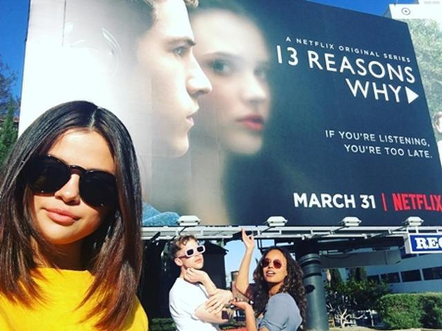 画像: 『13の理由』の看板を背にポーズを決める3人。