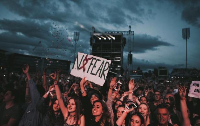画像: アリアナ主催の慈善公演で「No Fear(恐れない)」とテロに屈しないという意味のスローガンを書いたカードかざす観客たち。©Ariana Grande