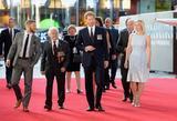 画像: 胸に勲章をたくさん着けた退役軍人の男性とともにお付きの人たちを従えてレッドカーペットを歩くヘンリー王子。