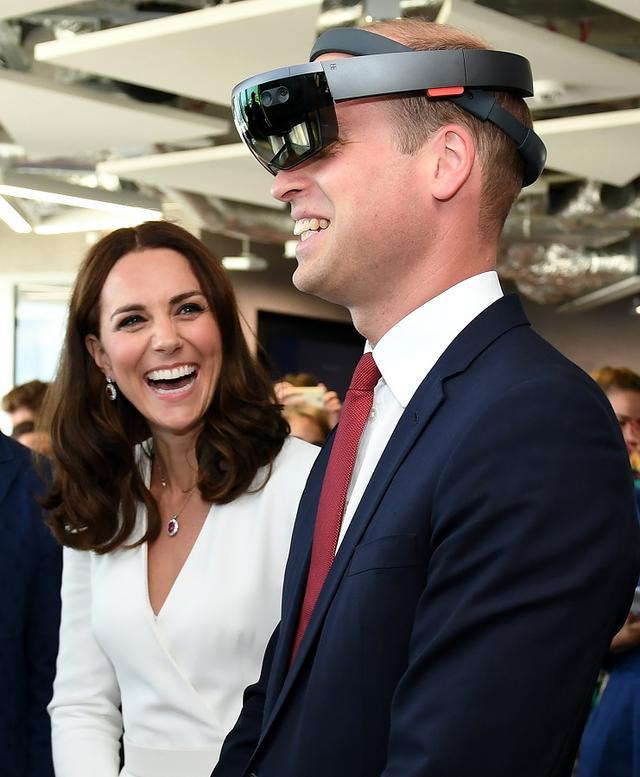 画像: 若手実業家が集まるレセプション・イベントでバーチャルリアリティを体験できるVRゴーグルを着用するウィリアム王子を楽しそうに見守るキャサリン妃。