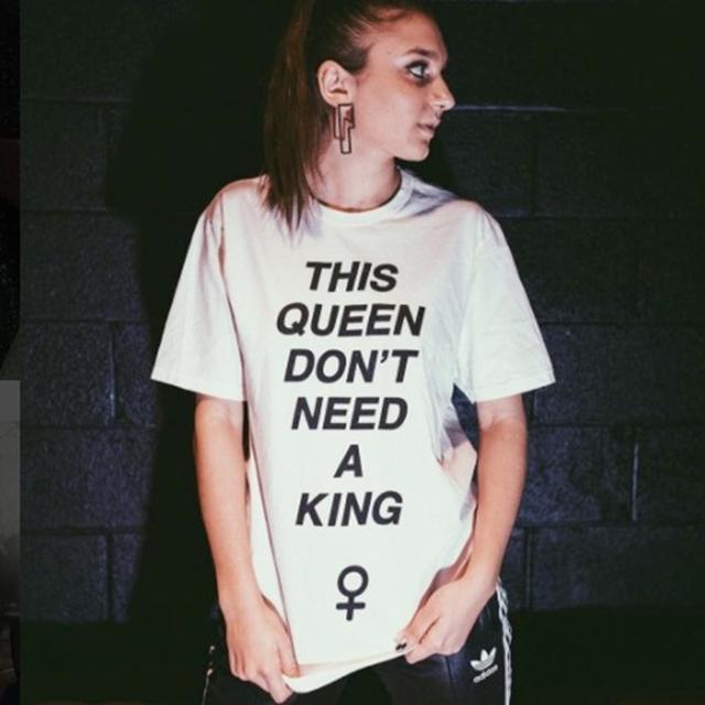 画像: 「私というクイーンに王は不要」という、「シット・スティル、ルック・プリティ」のリリックがプリントされたTシャツを着て
