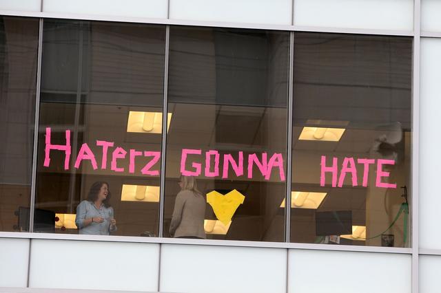 画像: 裁判所の向かいのビルの窓にポストイット(メモ帳)で作られた「Free Tay!(テイラーを開放しろ!)」、「Haterz (s) Gonna Hate(言いたい奴には言わせておけ/テイラーのヒット曲『シェイク・イット・オフ』の一節を引用)」というテイラーへの応援メッセージ。