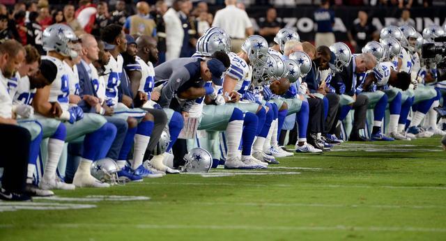 画像: 9月25日に行われた試合で、国家斉唱中にひざまずくダラス・カウボーイズの選手たち。
