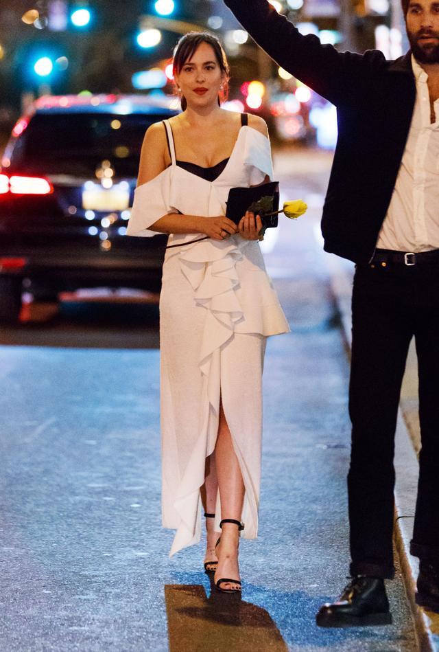 画像: ラッフルがほどこされた白のドレスで登場したダコタ。