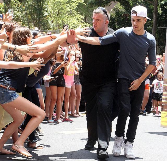 画像: リアムに触れようと近づくファンたちを制止するボディーガード。
