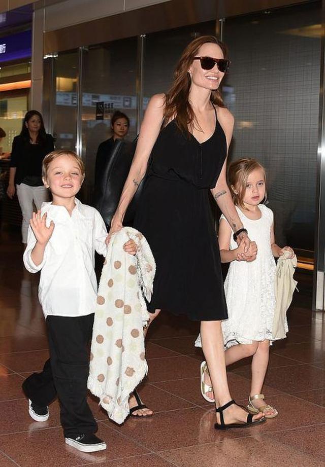 画像: 2014年夏の来日時には何人かの子供たちを連れて来日したアンジェリーナ。双子のノックス(左)とヴィヴィアン(右)と手をつないで羽田空港に降りたった。