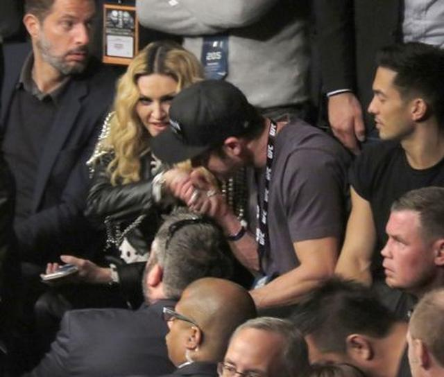 画像: 横にいる男性が見守るなか、ザックがマドンナの右手を掴み…