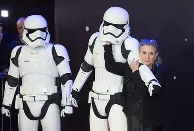画像: 映画『スター・ウォーズ/フォースの覚醒』のプレミアにて。ストーム・トルーパーとじゃれるキャリー。