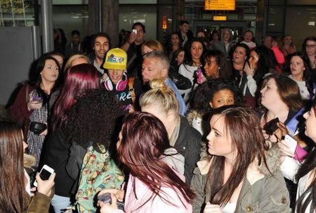 画像: 2012年ロンドンの空港ですごい数のファンに囲まれるジャスティン。