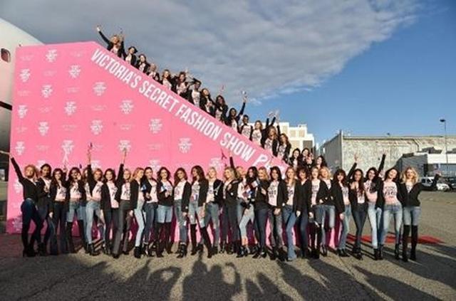 画像: 今回ランウェイを歩くヴィクシーモデルたちがタラップと地上に大集合し、記念撮影。みんなおそろいのピンクのTシャツを着用。