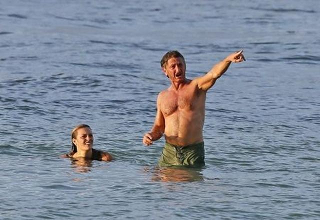 画像: ビーチの方を指さして何からシャウト。