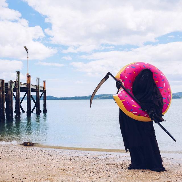 画像: ドーナツ型の浮き輪を持つ死神。