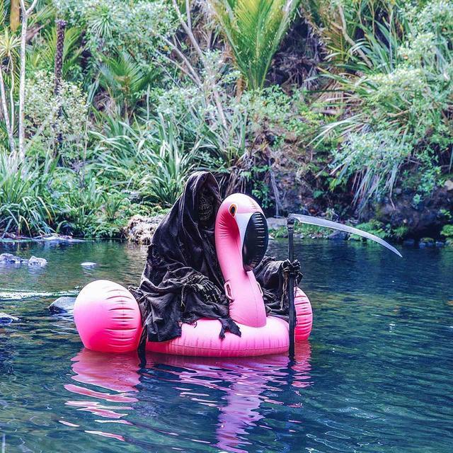 画像: フラミンゴの浮き輪に乗る死神。