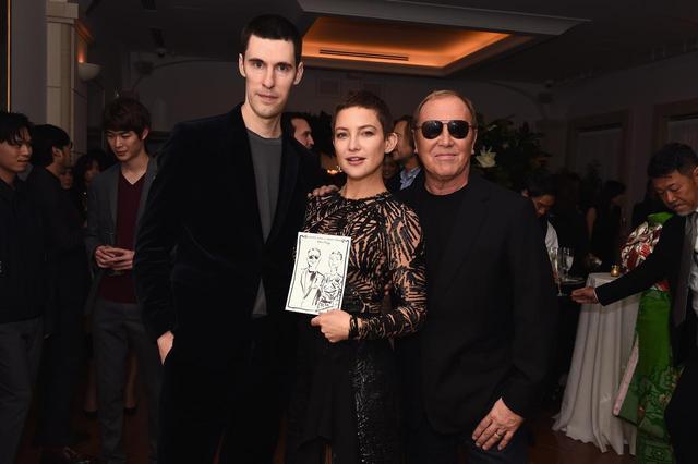 画像: (左から)英国アーティストのクリム・エバンデンと、クリムが描いたイラストを持ったケイト・ハドソン、マイケル・コース