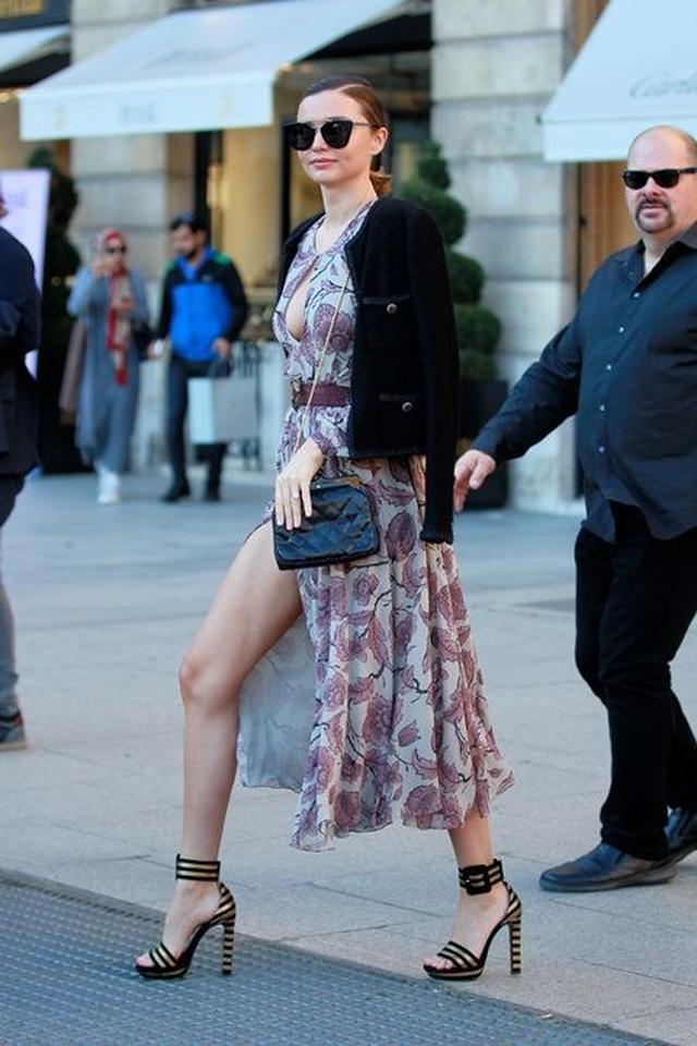 画像: 撮影中よりも高いヒールを穿き、大胆に空いたスリットから脚をのぞかせて歩くミランダ。胸元もスーパーローカットで、とにかく広場中の視線を集めていた。