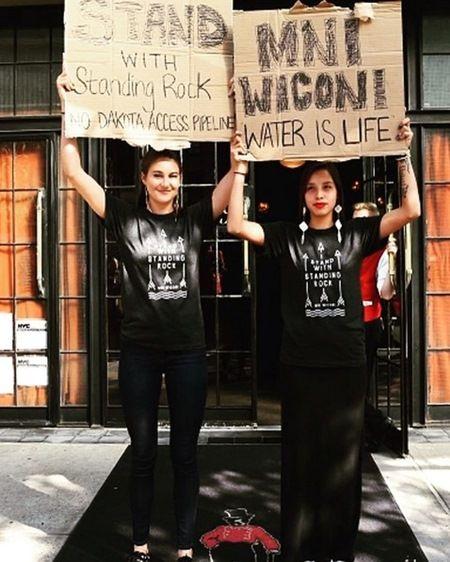 画像: NYで「私はスタンディング・ロックを応援する。ダコタ・パイプライン反対」というプラカードを掲げて(左)。