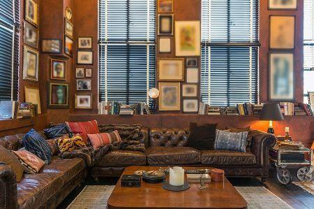 画像: 無数のアートが飾られ、革張りのソファが置かれたシアタールーム。