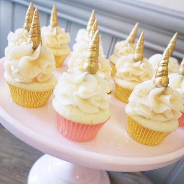 画像: 「ホールケーキはちょっと手がかかりすぎる…」という人には、より手軽に作れるカップケーキがおすすめ。白い生地のケーキにクリームを乗せたら、マジパンで作ったゴールドの角をトッピングしてグリッターパウダーをかけて。 Ⓒsweetnsaucyshop