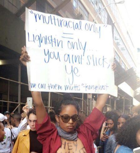 画像: 参加者に混じり、オーディションの参加条件に抗議するプロテスターの姿も。「複数以上の血を引く人=明るめの肌色の人ってことなんだろ!クールじゃないよ、カニエ!」と書かれたプラカードを掲げる女性。 Ⓒladybreec