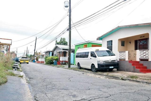 """画像: """"リアーナ・ドライブ""""と名称変更されたリアーナの幼少期の自宅前の通り。手前の赤茶の階段の家がリアーナの家。©George Alleyne"""