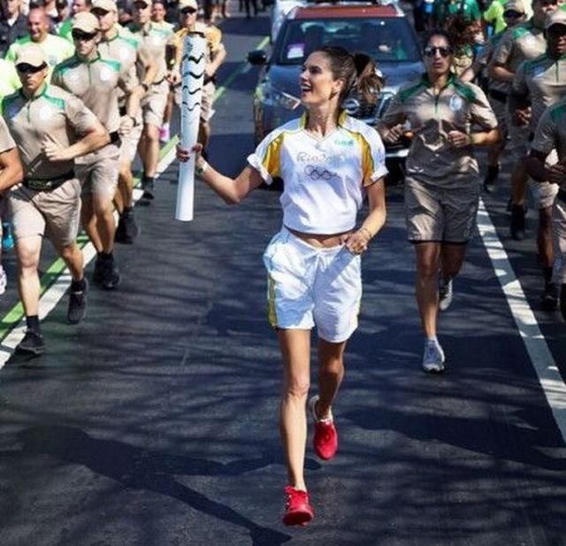 画像: アレッサンドラは、笑顔で聖火ランナーを。